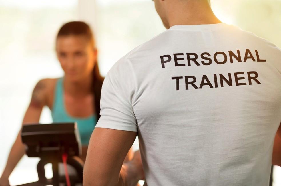 Personal trainer con ragazza su cyclette