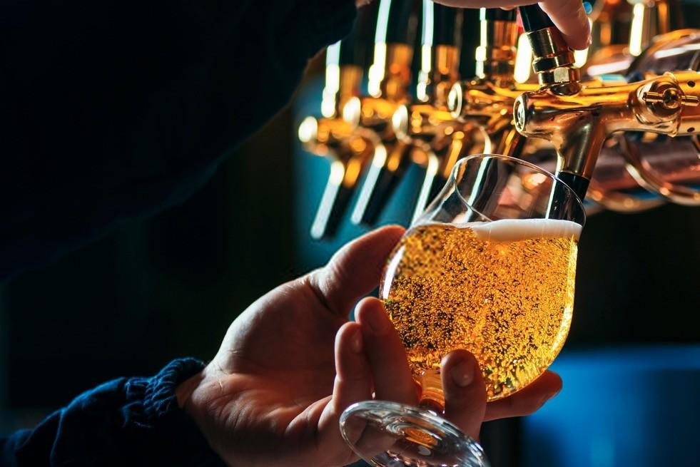 Bicchiere con birra versata da spillatore
